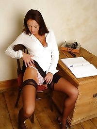 Vickie Powell in secretary outfit with specs and stockings.