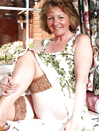 Sue in a flowery dress and tanned stockings