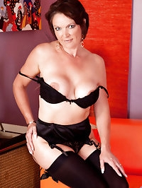 Busty mature milf Foxy bends over showing off her shaved..